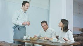 Pares jovenes que disfrutan de su almuerzo en el restaurante cuando camarero que trae más comida almacen de metraje de vídeo