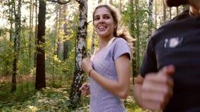 Pares jovenes que disfrutan de su funcionamiento apacible en el bosque metrajes