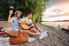 Pares jovenes que disfrutan de su tiempo, teniendo comida campestre romántica en la playa Tocar la guitarra y canto foto de archivo