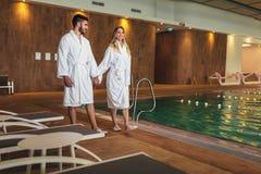 Pares jovenes que disfrutan de tratamientos y que se relajan en el centro del balneario de la salud imagen de archivo