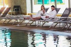 Pares jovenes que disfrutan de tratamientos y que se relajan en el centro del balneario de la salud imagen de archivo libre de regalías