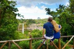 Pares jovenes que disfrutan de una opinión el las caídas de Chamarel de Mauricio imagen de archivo