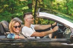 Pares jovenes que disfrutan de viaje por carretera dentro de su coche convertible fotografía de archivo
