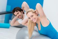 Pares jovenes que ejercitan en un gimnasio Fotografía de archivo libre de regalías