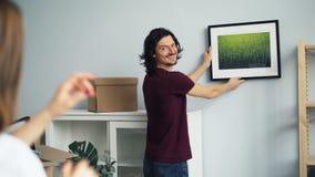 Pares jovenes que eligen el lugar para la imagen en la pared en nueva casa después de la relocalización almacen de metraje de vídeo