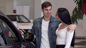 Pares jovenes que eligen el nuevo coche en la representación, mirando dentro del automóvil almacen de video