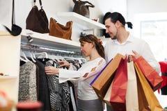 Pares jovenes que eligen la ropa en el mercado Fotografía de archivo libre de regalías