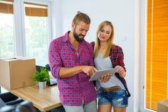 Pares jovenes que eligen los muebles a su nuevo apartamento usando TA foto de archivo