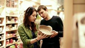 Pares jovenes que eligen platos en tienda de la alameda de compras metrajes