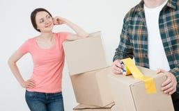 Pares jovenes que embalan sus cosas en cajas de cartón Foto de archivo libre de regalías