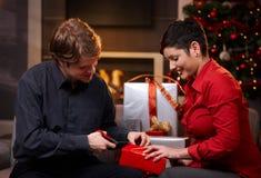 Pares jovenes que envuelven regalos de Navidad imagen de archivo libre de regalías