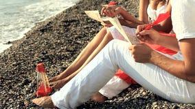 Pares jovenes que escriben letras románticas en la playa almacen de metraje de vídeo
