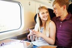 Pares jovenes que escuchan la música en viaje de tren Foto de archivo libre de regalías