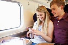 Pares jovenes que escuchan la música en viaje de tren Imagen de archivo