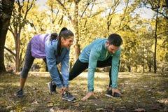 Pares jovenes que estiran antes de correr en parque de la ciudad En el movimiento fotografía de archivo libre de regalías