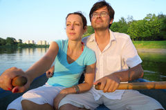 Pares jovenes que flotan rio abajo en un barco Imagen de archivo libre de regalías