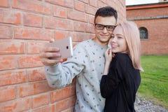 Pares jovenes que fotografían un selfie con smartphone en el fondo de la pared de ladrillo roja Muchacha rubia con ojos azules y  Fotos de archivo libres de regalías