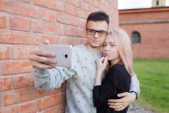Pares jovenes que fotografían un selfie con smartphone en el fondo de la pared de ladrillo roja Muchacha rubia con ojos azules y  Imagenes de archivo