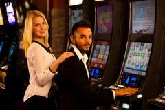 Pares jovenes que ganan en la máquina tragaperras en casino foto de archivo