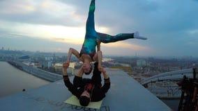 Pares jovenes que gozan de la adrenalina de la yoga acrobática encima del alto puente almacen de metraje de vídeo