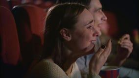 Pares jovenes que gozan de la película en cine Pares que comen las palomitas y que miran película almacen de metraje de vídeo