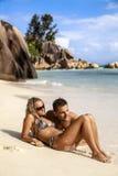 Pares jovenes que gozan de la playa Imagenes de archivo