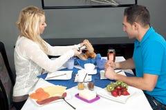Pares jovenes que gozan de un desayuno del hotel Foto de archivo libre de regalías