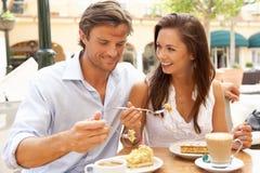 Pares jovenes que gozan del café y de la torta Imagen de archivo libre de regalías