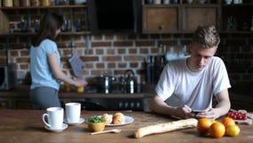 Pares jovenes que gozan del desayuno en cocina almacen de metraje de vídeo