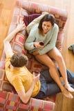 Pares jovenes que gozan del vino rojo en el sofá Fotos de archivo libres de regalías