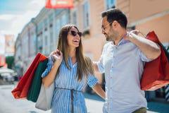 Pares jovenes que gozan en compras, divirti?ndose en la ciudad foto de archivo libre de regalías