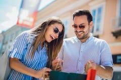 Pares jovenes que gozan en compras, divirti?ndose en la ciudad fotos de archivo libres de regalías