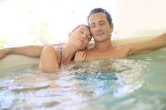 Pares jovenes que gozan y que se relajan en balneario Fotos de archivo libres de regalías