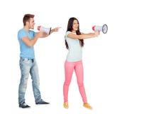 Pares jovenes que gritan con los megáfonos Fotografía de archivo libre de regalías