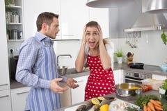 Pares jovenes que gritan en casa en la cocina Imagen de archivo