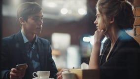 Pares jovenes que hablan animadamente, café de consumición que tiene una fecha en un nuevo café moderno agradable en centro de c metrajes