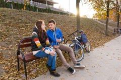 Pares jovenes que hablan en banco en parque en la puesta del sol Imágenes de archivo libres de regalías