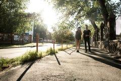 Pares jovenes que hablan en la puesta del sol en un ambiente urbano Foto de archivo libre de regalías