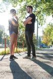 Pares jovenes que hablan en la puesta del sol en un ambiente urbano Fotografía de archivo libre de regalías