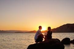 Pares jovenes que hablan en una roca por el mar Imágenes de archivo libres de regalías