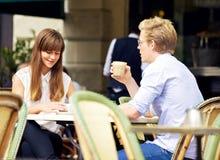 Pares jovenes que hablan sobre una taza de café Imágenes de archivo libres de regalías