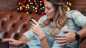 Pares jovenes que hacen compras en línea en casa el Nochebuena