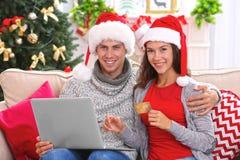 Pares jovenes que hacen compras en línea con la tarjeta de crédito en casa para la Navidad Foto de archivo libre de regalías