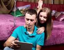 Pares jovenes que hacen compras en línea usando la tableta digital Junte la risa, la muchacha que miente en la cama en casa y al  Foto de archivo