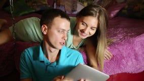 Pares jovenes que hacen compras en línea usando la tableta digital Junte la risa, la muchacha que miente en la cama en casa y al  almacen de metraje de vídeo