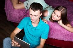 Pares jovenes que hacen compras en línea usando la tableta digital Junte la risa, la muchacha que miente en la cama en casa y al  Imágenes de archivo libres de regalías