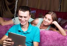 Pares jovenes que hacen compras en línea usando la tableta digital Junte la risa, la muchacha que miente en la cama en casa y al  Imagen de archivo libre de regalías