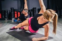 Pares jovenes que hacen ejercicios en clase de la aptitud Imagen de archivo libre de regalías