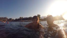 Pares jovenes que hacen el autorretrato en el mar durante vacaciones de verano Pares sonrientes felices que nadan junto en el océ metrajes