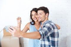 Pares jovenes que hacen el selfie que lleva a cabo llaves en nuevo plano Imagen de archivo libre de regalías